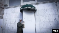 "A woman stands below the awning of an Ahmadi mosque in Brooklyn, New York. ""Love for all, hatred for none,"" the banner reads. (R. Taylor/VOA)"