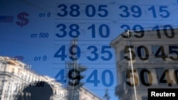 FILE - A woman is reflected in a window with a board displaying currency exchange rates in St. Petersburg, Russia.