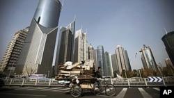在上海的高樓大廈之間,一個男子騎著三輪車在收廢品,貧富差距令人擔憂 。
