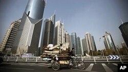 在上海的高樓大廈之間,一個男子騎著三輪車在收廢品,貧富差距令人擔憂
