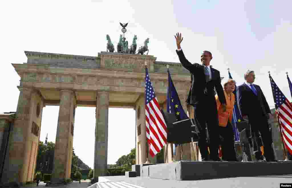 Flanked by Chancellor Angela Merkel and Berlin Mayor Klaus Wowereit, U.S. President Barack Obama waves at the Brandenburg Gate in Berlin June 19, 2013.
