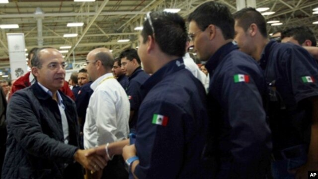 Handout picture provided by the Mexican Presidency shows Mexican President Felipe Calderon (L) shaking hands with workers during a tour at the new Chrysler automaker plant in Saltillo, Cohauila state, Mexico, 29 Oct 2010