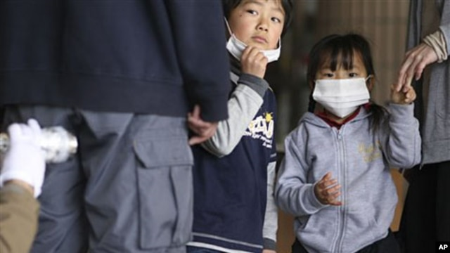Children watch their father is screened for radiation at a shelter in Fukushima prefecture, Japan, March 29, 2011