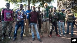 FILE - 'Anti-Balaka' fighters stand for a photo in Boda, Central African Republic, Aug. 28, 2014.