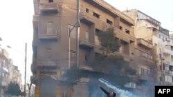 Демонстрант отбрасывает дымовую шашку в сторону позиций сил безопасности. Город Хомс. 27 декабря 2011 г.