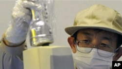 A staff member checks the level of radiation on an industrial product produced in Fukushima Prefecture at Fukushima Technology Center in Koriyama, northeastern Japan, April 4, 2011