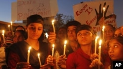 Warga di Ahmadabad, India, menyalakan lilin dalam aksi protes mengecam pemerkosaan beramai-ramai atas seorang perempuan di New Delhi. (AP/Ajit Solanki)