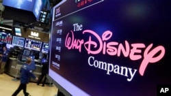 FILE - The Walt Disney Co. logo appears on a screen above the floor of the New York Stock Exchange, Aug. 8, 2017.