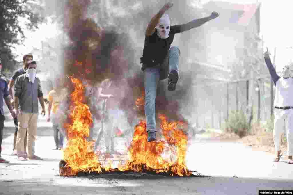 سری نگر میں مظاہرے کے دوران احتجاج کرنے والا ایک نوجوان جلتے ہوئے ٹائر پر سے کود رہا ہے۔
