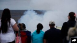 Visitors watch as steam and gas rise from Kilauea's summit crater in Volcanoes National Park, Hawaii, May 9, 2018.