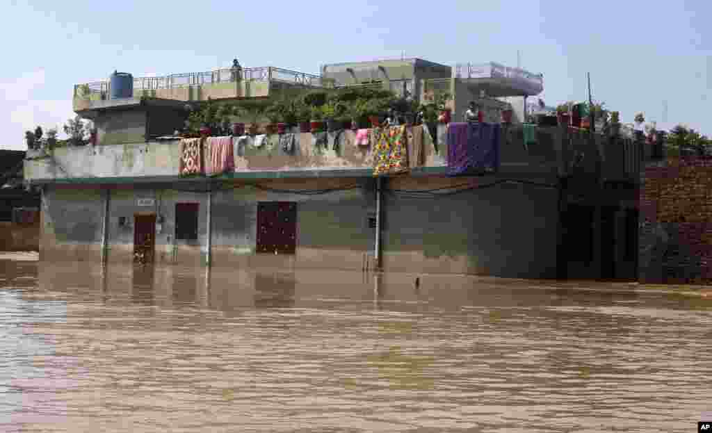 Residents wait on the top floor of their deluged house following heavy monsoon rains in Wazirabad, some 100 kilometers (65 miles) north of Lahore, Pakistan, Sept. 7, 2014.