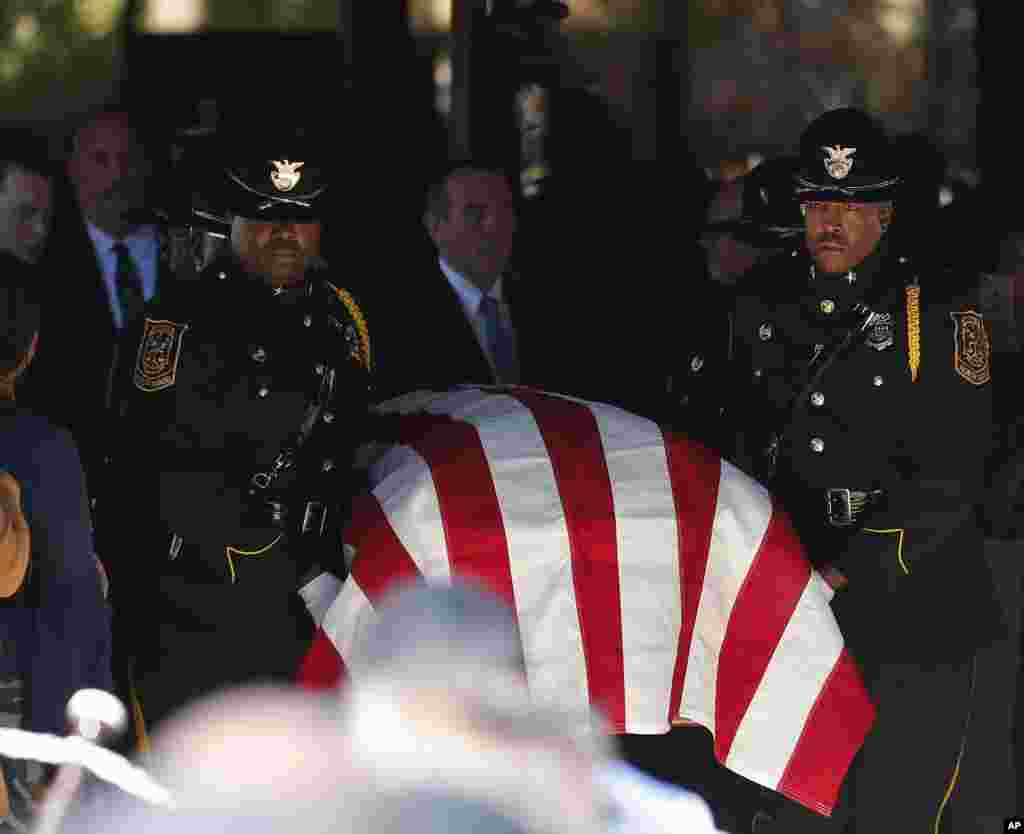 A police honor guard carries the casket out of All Saints Catholic Church after funeral service for Dekalb County Police officer Edgar Flores, in Dunwoody, Ga.