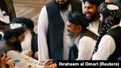 Les délégués des talibans se saluent à l'entame des négociations avec le gouvernement afghan à Doha, au Qatar, le 12 septembre 2020. (Photo: REUTERS/Ibraheem al Omari)