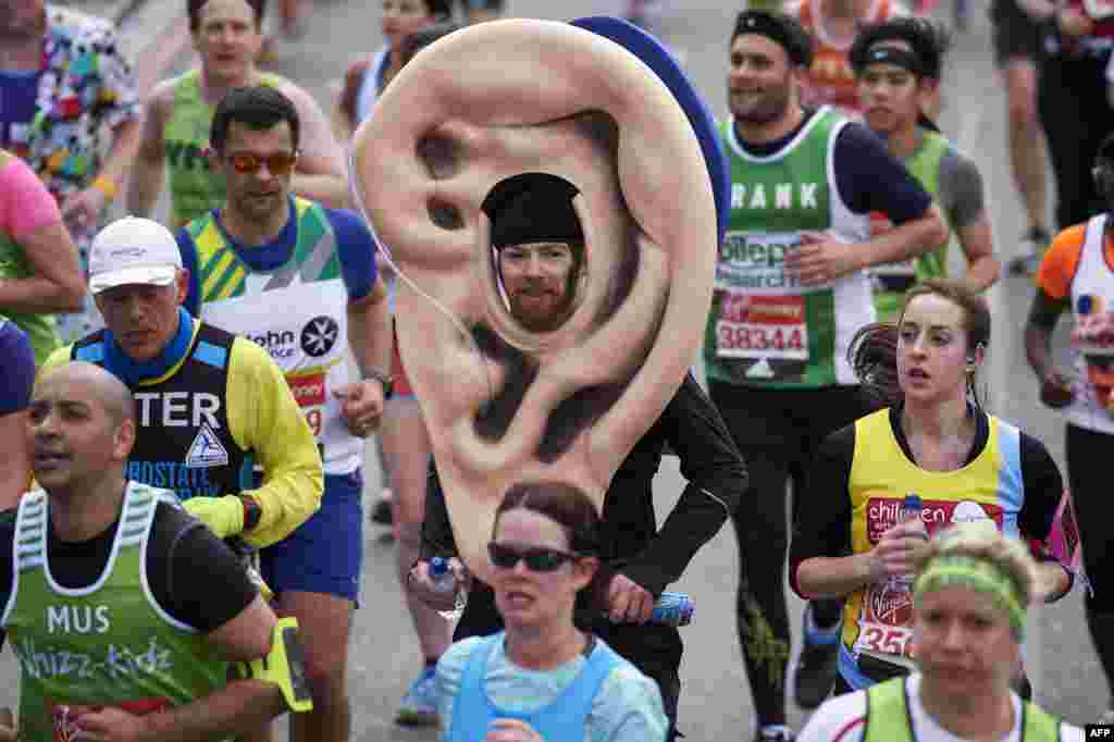 A runner in a fancy ear costume takes part in the 2016 London Marathon in central London.