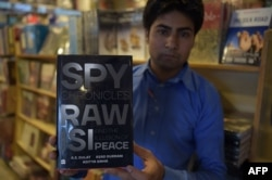 "FILE - A Pakistani salesman shows ""Spy Chronicles: RAW, ISI and the Illusion of Peace,"" co-written by Asad Durrani, a retired Pakistani army officer, at a bookstore in Islamabad, May 30, 2018."