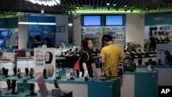 Sebuah pasangan melihat-lihat ponsel di sebuah toko di Beijing. (Foto: Dok)