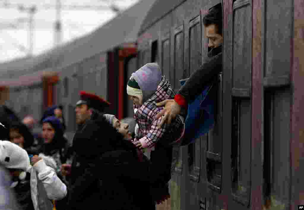 A refugee man passes a baby to a woman from a train window, upon their arrival at the transit center for refugees near northern Macedonian village of Tabanovce.