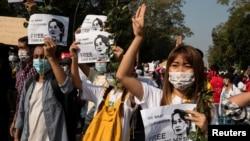 缅甸仰光的示威者致象征反政变抗议的三指礼,另一只手拿着缅甸国务资政昂山素季的画像,要求军政府释放这位诺贝尔和平奖得主。