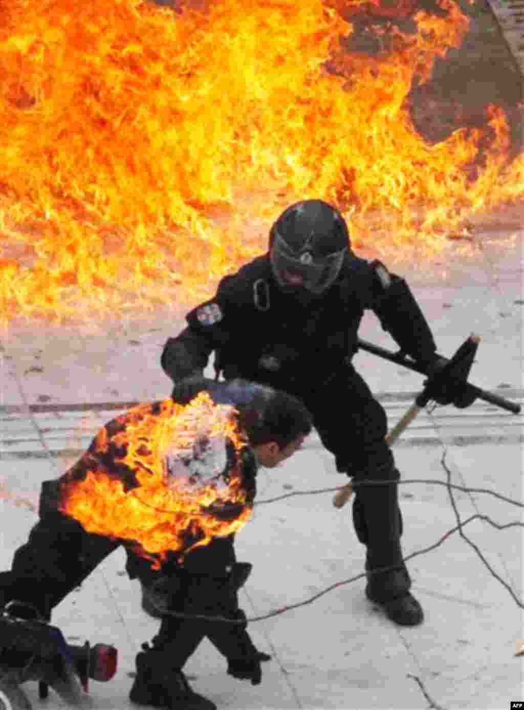 A motorcycle policeman burns, front, as his colleague tries to help him after protesters threw a petrol bomb in Athens, Wednesday, Feb. 23, 2011. Scores of youths hurled rocks and petrol bombs at riot police after clashes broke out Wednesday during a mass