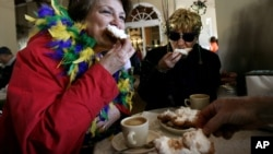 Dressed for Mardi Gras, friends enjoy beignets and coffee at the famous Cafe Du Monde in New Orleans.