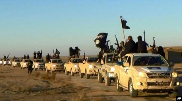 FILE - In this undated file photo released by a militant website, which has been verified and is consistent with other AP reporting, militants of the Islamic State group hold up their weapons and wave flags on their vehicles in a convoy on a road leading to Iraq, while riding in Raqqa, Syria.