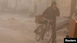 Seorang pria menutupi mukanya sambil menuntun sepedanya, saat badai debu melanda Aleppo, Suriah (foto: dok).