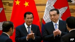 In this photo taken on Jan. 22, 2019, Cambodian Prime Minister Hun Sen, center left, applauds with Chinese Premier Li Keqiang during a signing ceremony at the Great Hall of the People in Beijing, China.