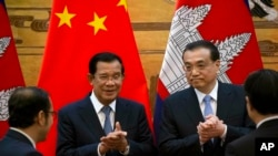 Cambodian Prime Minister Hun Sen, center left, applauds with Chinese Premier Li Keqiang during a signing ceremony at the Great Hall of the People in Beijing, China, Tuesday, Jan. 22, 2019.