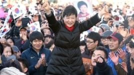 South Korea's presidential candidate Park Geun-hye of ruling Saenuri Party raises her arms  during her presidential election campaign in Busan, South Korea, December 18, 2012.