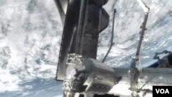 Gambar dari televisi NASA menunjukkan pesawat Atlantis saat merapat ke Stasiun Antariksa Internasional (10/7).