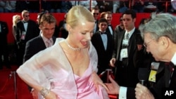 British actress Gwyneth Paltrow lifts the hem of her skirt to speak to a television reporter as she arrives for the 71st annual Academy Awards ceremony, March 21, 1999 in Los Angeles.