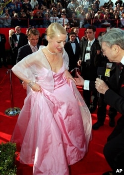 British actress Gwyneth Paltrow lifts the hem of her skirt to speak to a television reporter as she arrives for the 71st annual Academy Awards ceremony, March 21, 1999, in Los Angeles.