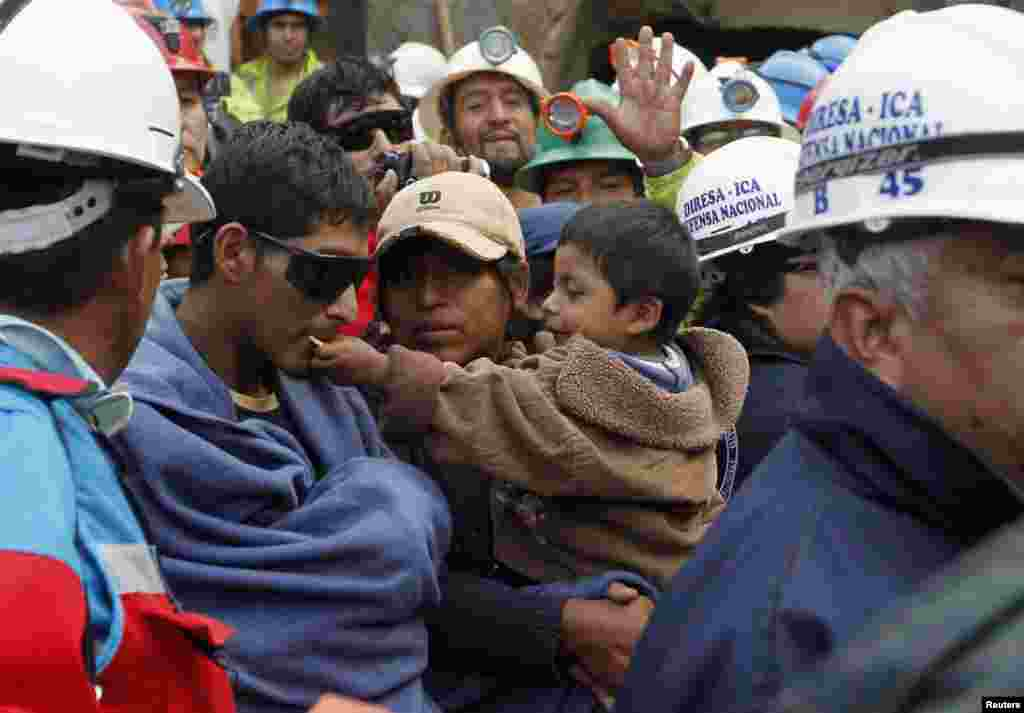 """El minero Josue Tapia es reconfortado por su esposa e hijo luego de haber sido restacatado de la mina """"Cabeza de Negro""""."""