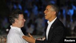 ປະທານາທິບໍດີໂຄລົມເບຍ ທ່ານ Juan Manuel Santos (ຊ້າຍ) ຈັບມືກັບປະທານາທິບໍດີສະຫະລັດ ທ່ານ Barack Obama ໃນຂະນະທີ່ໄປເຖິງທຳນຽບ San Felipe Castle ເພື່ອຮັບປະທານອາຫານຮ່ວມກັນກ່ອນ ກອງປະຊຸມສຸດຍອດ ຂອງບັນດາປະເທດໃນປະວີບອາເມຣິກາ ທີ່ເມືອງ Cartagena, ວັນທີ 13, ເດືອນເມສາ 2012