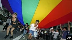 Participants hold a giant rainbow flag to symbolize lesbian, gay, bisexual, and transgender rights during a parade in Hong Kong, November 2011. (file photo)