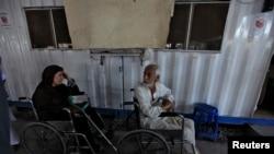 افغان مہاجرین پشاور میں اقوام متحدہ کے ایک مرکز کے باہر بیٹھے ہیں۔ فائل فوٹو