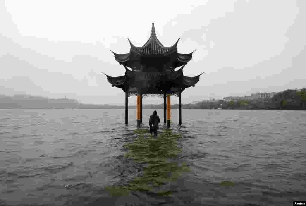 A man walks towards a flooded pavilion by the overflowing West Lake after Typhoon Fitow hit Hangzhou, Zhejiang province, China, Oct. 8, 2013.