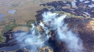FILE -  In this June 7, 2015 file photo, smoke rises from the Bogus Creek Fire, one of two fires burning in the Yukon Delta National Wildlife Refuge in southwest Alaska.