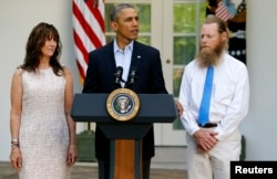 FILE - President Barack Obama stands with Bob Bergdahl, right, and Jami Bergdahl, left, as he delivers a statement about the release of their son, prisoner of war U.S. Army Sergeant Bowe Bergdahl, in the Rose Garden at the White House in Washington, May 31, 2014.
