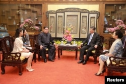 Kim Jong Un y su esposa Ri Sol Ju (izquierda) conversan con el presidente chino, Xi Jinping, y su esposa, Peng Liyuan.