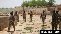 FILE - Soldiers walk among the ruins of the Government Secondary School in Chibok, Nigeria, March 25, 2016.
