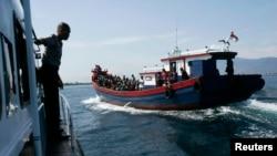 Polisi mengawasi perahu kayu yang membawa pengungsi Rohingya dari Myanmar. Pemerintah Australia mengatakan kebijakan mereka tidak mengijinkan pencari suaka membahayakan keselamatan hidup mereka untuk tiba di Australia dengan menggunakan perahu.