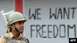 سری نگر میں ایک سیکیورٹی اہل کار کرفیو کے دوران ازادی کے نعرے کے ساامنے کھڑا ہے۔ فائل فوٹو