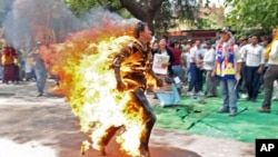 Jamphel Yeshi, a Tibetan exile, runs after setting himself on fire during a protest against the upcoming visit of Chinese President Hu Jintao to India in New Delhi, March 26, 2012.