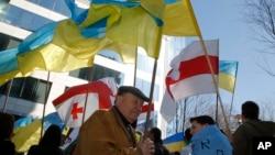 Manifestantes pro-Ucrania ondean banderas durante una protesta en las afueras de la cumbre de la UE en Bruselas.