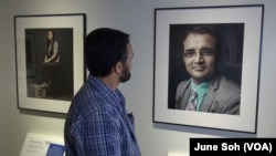 Tara Dhungana looks at his own portrait and story, one of the 20 on display at the Ohio History Center. Dhungana is now a restaurant owner in Columbus, and he sees the exhibit as a way to recapture some of the history his people have lost.