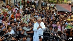 Bihar Chief Minister Nitish Kumar, center, greets supporters after victory in Bihar state elections Nov. 8, 2015. (AP Photo/Aftab Alam Siddiqui)