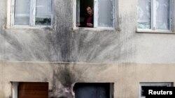 Glavni i odgovorni urednik Vijesti Mihailo Jovović gleda kroz prozor redakcije podgoričkog dnevnika, oštećen u eksploziji bombe 27. decembra 2013.