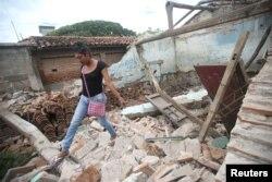 Una indígena zapoteca Muxe camina sobre los escombros de su casa destruida por el terremoto que estremeció la costa sur de México el jueves 7 de septiembre. Juchitán, Mexico, Sept. 10, 2017.