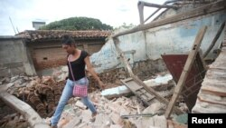 Peregrina, 26, an indigenous Zapotec transgender woman also know as muxe, walks on the debris of her house destroyed after an earthquake that struck on the southern coast of Mexico late Thursday, in Juchitan.